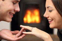 Paare, die einen Verlobungsring nach Antrag schauen Stockfotos