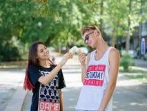Paare, die Eiscreme in einem Park essen Freund und Freundin auf einem unscharfen natürlichen Hintergrund Datierungskonzept Kopier lizenzfreie stockfotografie
