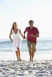 Paare, die entlang Sandy Beach Holding Hands laufen Lizenzfreies Stockbild