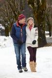 Paare, die entlang Snowy-Straße im Skiort gehen Stockfotos