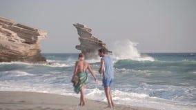 Paare, die entlang Sommer-Strand bei Sonnenuntergang gehen stock footage