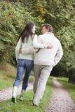 Paare, die entlang Waldpfad gehen Lizenzfreie Stockfotos