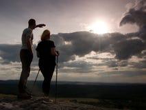 Paare, die erstaunliche Momente während des Sonnenuntergangs genießen Junge Paare Wanderer auf der Spitze der Felsenuhr zu Sun Lizenzfreie Stockfotos