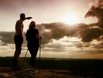 Paare, die erstaunliche Momente während des Sonnenuntergangs genießen Junge Paare Wanderer auf der Spitze der Felsenuhr zu Sun Lizenzfreies Stockfoto