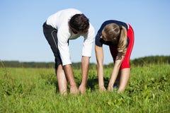 Paare, die für Übung am Sommer aufwärmen Stockfoto