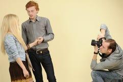 Paare, die für Fotografen aufwerfen Stockbild