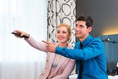 Paare, die Fernsehen mit Fernbedienung im Hotelzimmer schalten lizenzfreies stockbild