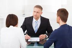 Paare, die Finanzberater konsultieren Lizenzfreie Stockbilder