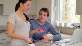Paare, die Finanzen am Laptop besprechen und Kreditkarte schneiden stock footage