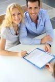 Paare, die Finanzvertrag unterzeichnen Stockfotos