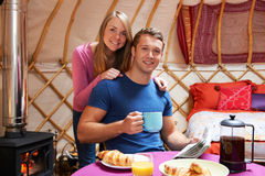 Paare, die Frühstück genießen, während, kampierend in traditionellem Yurt Stockfoto