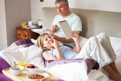 Paare, die Frühstück im Bett mit Papier- und Digital-Tablet essen Lizenzfreies Stockfoto