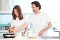 Paare, die Frühstück kochen stockbild