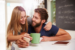 Paare, die Frühstück unter Verwendung Digital-Tablets und -telefons essen stockfoto