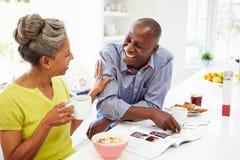 Paare, die frühstücken und Zeitschrift in der Küche lesen stockbilder
