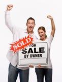 Paare, die für Verkaufszeichen zujubeln und anhalten Stockbilder