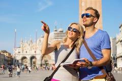 Paare, die Fremdenführer reisen und lesen Stockbild