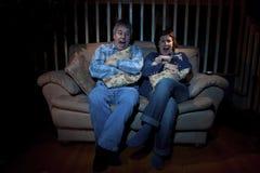 Paare, die furchtsamen Film überwachen stockfotos
