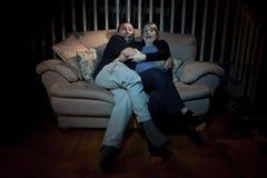Paare, die furchtsamen Film auf Fernsehapparat überwachen Stockbilder
