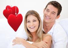 Paare, die gegen weißen Hintergrund sich umfassen Stockbilder