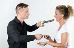Paare, die Geld gegen Schokolade austauschen Stockfotos