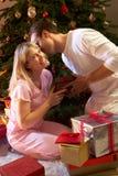 Paare, die Geschenke vor Baum austauschen Stockfoto