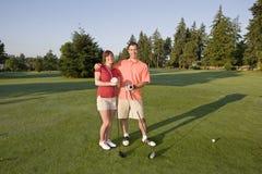 Paare, die Golf auf dem Kurs - horizontal spielen Lizenzfreies Stockfoto