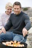 Paare, die Grill auf einem Strand kochen Lizenzfreie Stockfotos