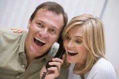 Paare, die gute Nachrichten über dem Telefon empfangen Lizenzfreie Stockfotos