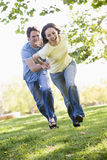 Paare, die Hände draußen anhalten und lächeln laufen lassen Stockbild