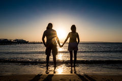 Paare, die Hand bei Ozeansonnenuntergangsonnenaufgang halten Stockbilder