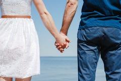 Paare, die Hand in Hand auf dem Strand halten Lizenzfreies Stockfoto
