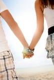 Paare, die Hand in Hand auf Sommerstrand gehen Lizenzfreies Stockbild
