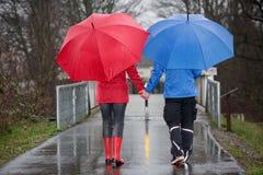 Paare, die Hand in Hand in den Regen gehen Stockfotografie