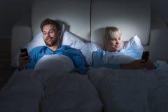 Paare, die Handys im Schlafzimmer halten Stockfotos