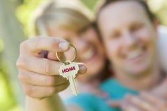 Paare, die Haus-Schlüssel mit Haupttext halten Stockbilder