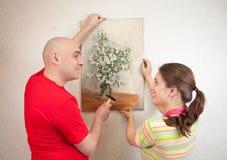 Paare, die herauf eine Kunstabbildung auf ihrer Wand hängen Stockfotos