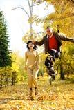 Paare, die in Herbstblätter springen Stockbilder