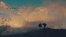 Paare, die Hilfe Schattenbild in den Bergen wandern Die wandernden Teamwork-Paare, helfen sich, vertrauen Unterst?tzung, Sonnenun stock video