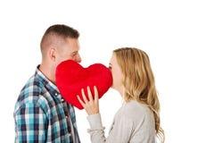 Paare, die hinter dem Kissen flüstern Lizenzfreies Stockbild