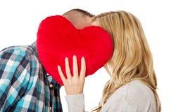 Paare, die hinter dem Kissen flüstern Stockbilder