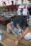 Paare, die hinter Hut im Café sich verstecken Lizenzfreies Stockbild
