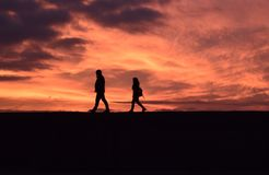 Paare, die hinunter einen sehr orange Sonnenuntergang gehen lizenzfreies stockfoto