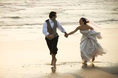 Paare, die hinunter Strand laufen. lizenzfreie stockfotos