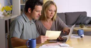 Paare, die ihre Finanzen mit Laptop tun Lizenzfreie Stockfotos