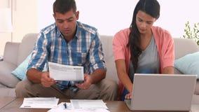 Paare, die ihre Rechnungen ausarbeiten stock video footage