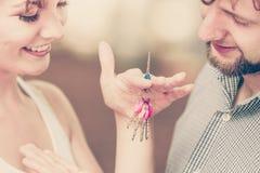 Paare, die ihre Schlüssel des neuen Hauses zeigen Stockfotografie