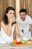 Paare, die im Bett frühstücken Stockbilder