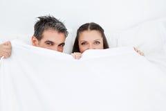 Paare, die im Bett hinter Blättern sich verstecken Stockbilder
