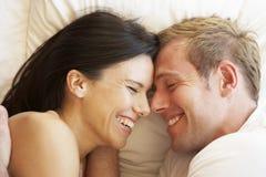 Paare, die im Bett sich entspannen stockbild